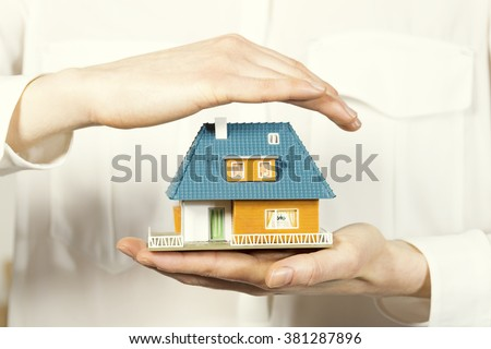 hand hovering small family house, home insurance concept - stock photo