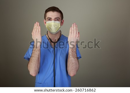 Hand Hygiene concept shot of a young male doctor holding his clean hands up ready for a procedure - stock photo