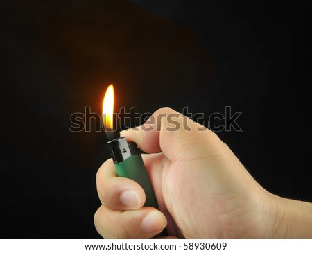 Hand Igniting Cigarette Lighter Isolated On Black Background - stock photo