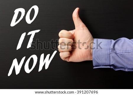 Hand in a business shirt giving the thumbs up sign to the words Do It Now in white text on a blackboard