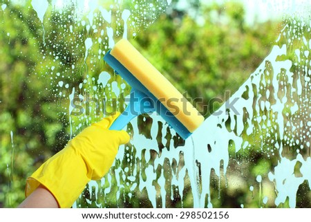 Hand in a yellow glove with special tool washes the soap window on the background of trees - stock photo