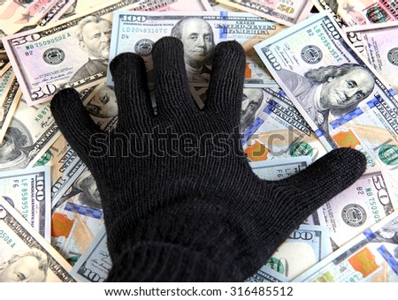Hand in Black Glove on the American Dollars Background - stock photo