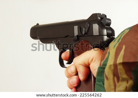 Hand in camouflage uniform with a semi-automatic pistol - stock photo