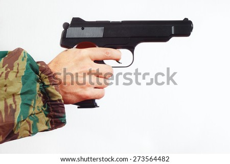 Hand in camouflage uniform with army pistol on a white background - stock photo