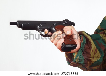 Hand in camouflage uniform with discharged army gun on a white background - stock photo