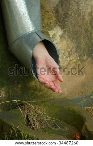 Hand in downspout - stock photo