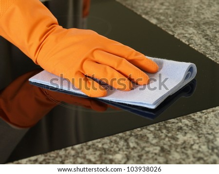 Hand in glove cleaning kitchen cooking top - stock photo