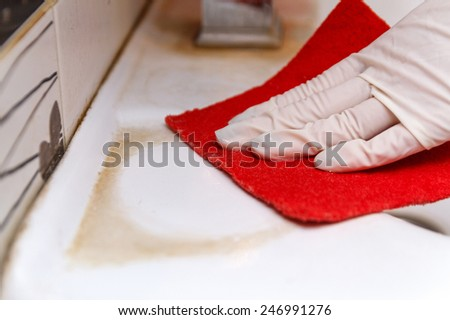 Hand in glove cleans dirty washbasin red sponge - stock photo