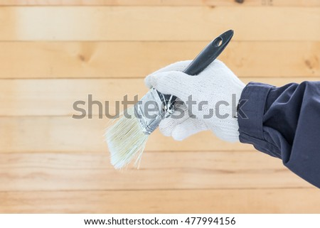 Hand in glove cotton holding brush paints with wall wood background