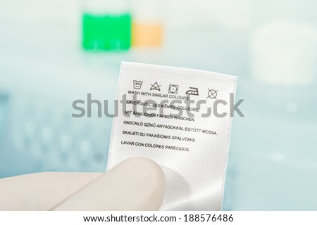 Hand in glove holding clothes laundry label on the background of a washing machine. Close up. - stock photo