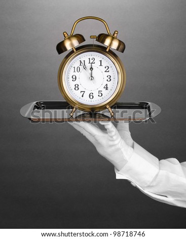 Hand in glove holding silver tray with alarm clock on grey background