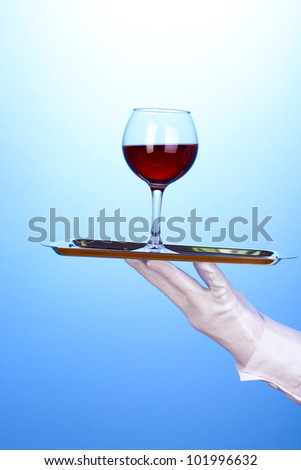 Hand in glove holding silver tray with wineglass on blue background - stock photo