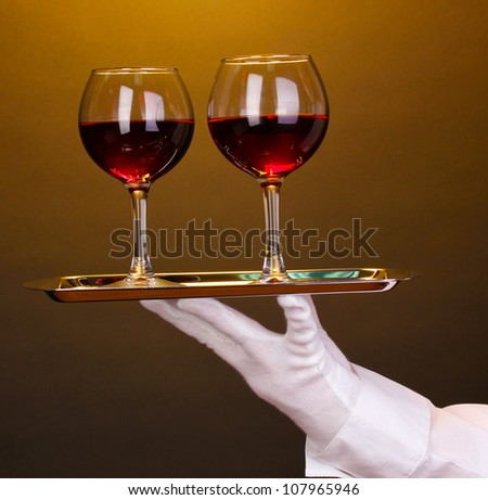 Hand in glove holding silver tray with wineglasses on brown background - stock photo