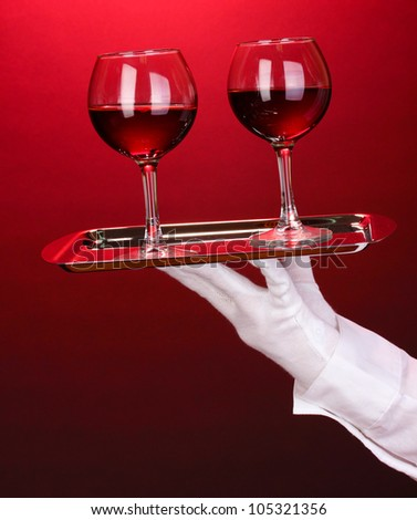 Hand in glove holding silver tray with wineglasses on red background - stock photo