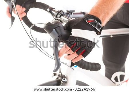 Hand in glove shifting bicycle's gears - stock photo