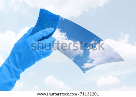 Hand in gloves cleaning the window with blue sponge - stock photo