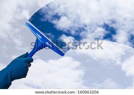 Hand in gloves holding squeegee and cleaning the blue sky. - stock photo