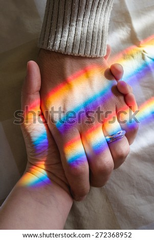 hand in hand with rainbow symbolizing endless love - stock photo