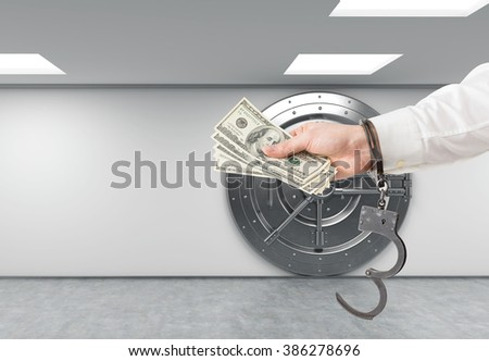 Hand in handcuffs holding money. Safe at background. Concept of financial crime. - stock photo