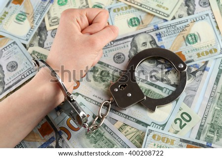 Hand in handcuffs on dollar banknotes. Corruption concept - stock photo