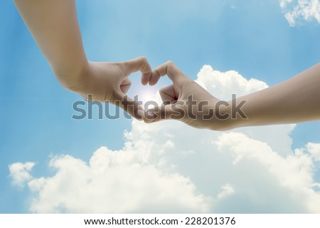 hand in love shape on sky background - stock photo