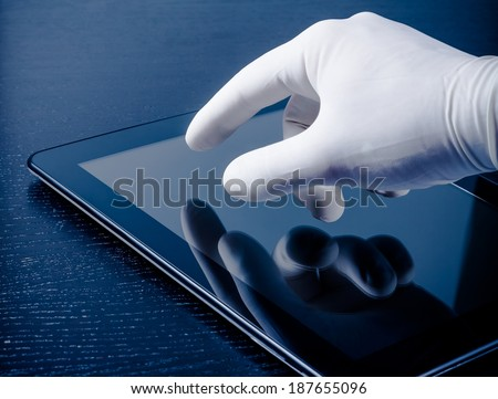 hand in medical glove touching modern digital tablet pc on wood table. Concept of medical or research theme - stock photo