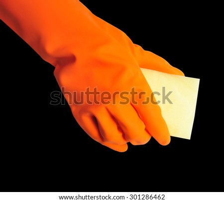 Hand in orange rubber glove with sponge isolated on black background. cleaning - stock photo