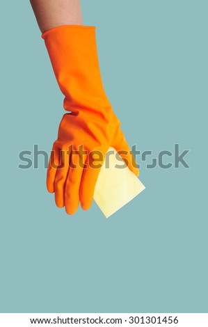 Hand in orange rubber glove with sponge isolated on blue background. cleaning - stock photo