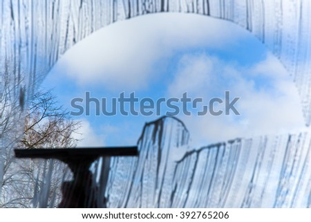 Hand in pink protective glove washing and cleaning window with professionally squeegee on background of cloudy sky.  Early spring windows cleaning. Maid cleans window. - stock photo