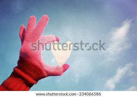 Hand in Pink striped glove holding a snow heart. Instagram effect. - stock photo