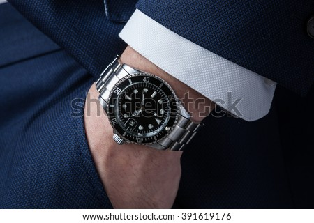 Hand in pocket with wrist watch in a business suit close up - stock photo