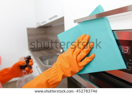 Hand in rubber glove cleans a new kitchen. Woman with housework, cleaning the kitchen. - stock photo