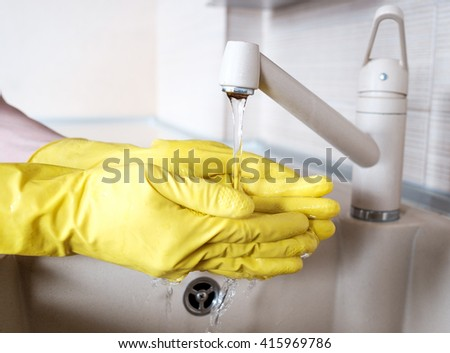 Hand in rubber glove in water stream at kitchen faucet - stock photo
