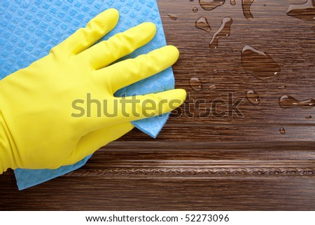 Hand in yellow glove with sponge, washing wooden surface - stock photo