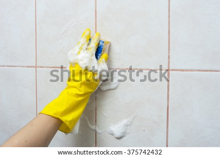 Hand in yellow gloves with sponge washing the tile. Cleaning concept.