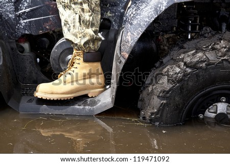 hand in yellow leather boot standing on the steps of the ATV standing in a muddy puddle - stock photo
