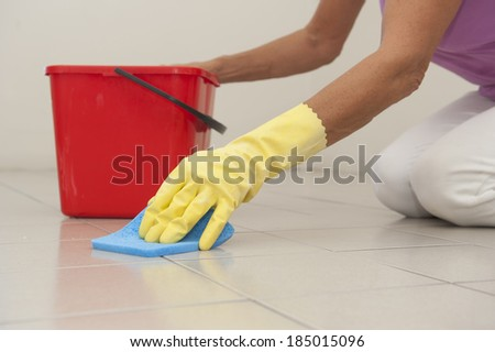 Hand in yellow rubber glove cleaning floor tiles with sponge, with woman, housewife in blurred background and copy space.