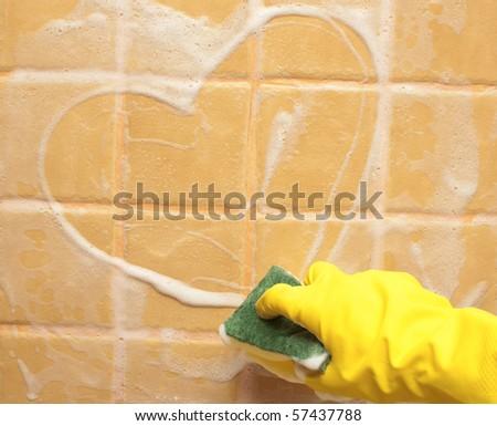 hand in yellow rubber glove draws heart - stock photo