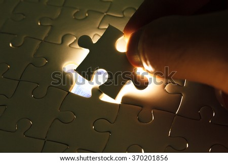 Hand insert missing jigsaw puzzle piece with light glow, business concept for completing the final puzzle piece - stock photo