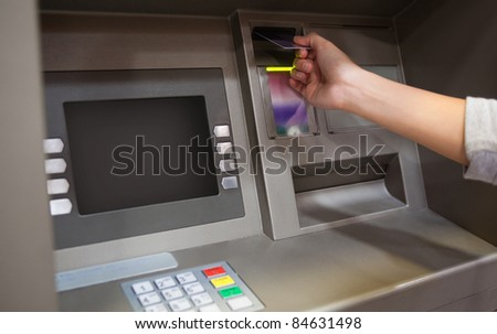 Hand inserting a credit card in an ATM - stock photo