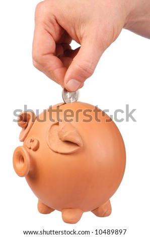 Hand inserting coin into piggy bank isolated on white
