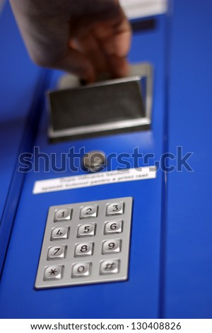 Hand inserting coin into vending machine - stock photo