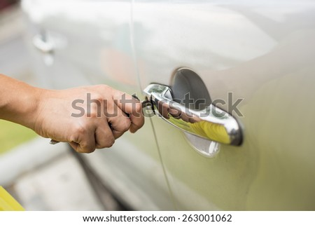 Hand inserting the key of the car - stock photo