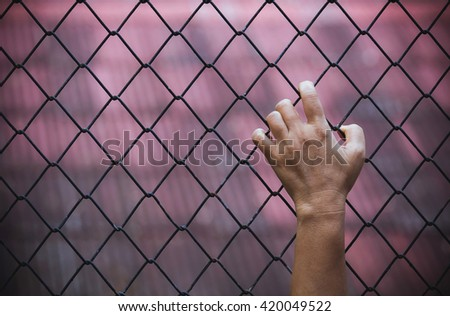 Hand inside iron fence with a sense of hopelessness and isolation.