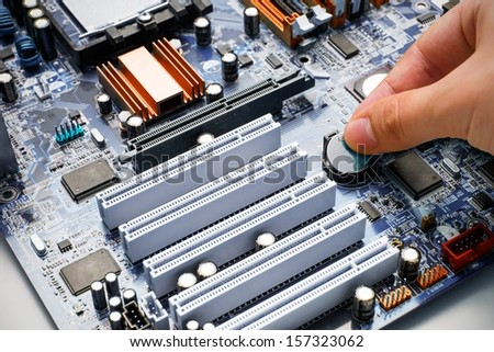Hand install battery to PC motherboard - stock photo