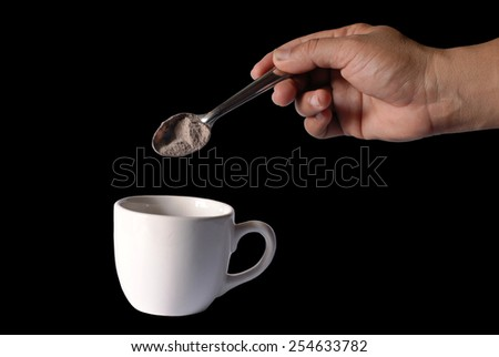 hand is filling coffee powder into a cup,black background - stock photo