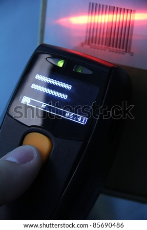 hand is holding a handheld barcode scanner - stock photo