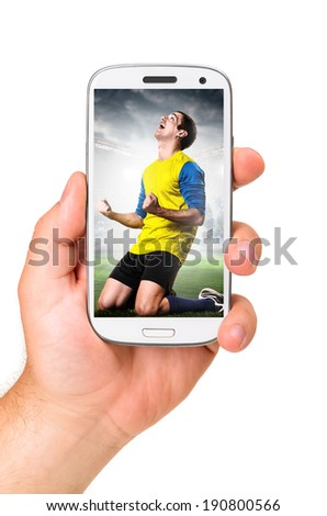 hand is holding a modern phone with soccer or football player celebrating on screen - stock photo