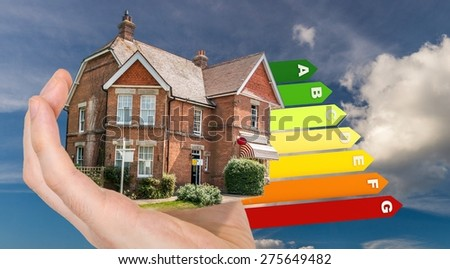 Hand is holding energy saving house with energy levels in background - stock photo