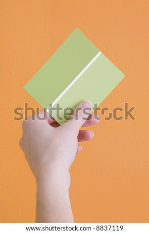 Hand is holding up a green paint sample to an orange wall. - stock photo